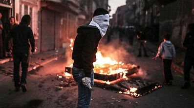 A masked protester holds a petrol bomb during clashes with Turkish police using water cannons and tear gas to disperse a demonstration in Istanbul protesting security operations against Kurdish rebels in southeastern Turkey on December 20, 2015. The number of Kurdish rebels killed in a massive Turkish military offensive in the restive southeast has jumped to 102, a security source told AFP, as the operation entered its fifth day. The government has imposed curfews in the mainly Kurdish towns of Cizre and Silopi as security forces battle militants linked to the Kurdistan Workers' Party (PKK). / AFP / Cagdas Erdogan