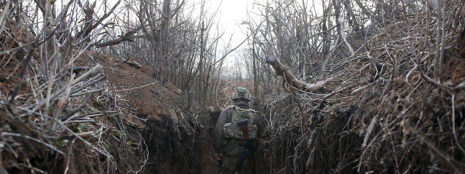 Ein ukrainischer Soldat patroulliert in einem Schützengraben in der Region Lugansk.