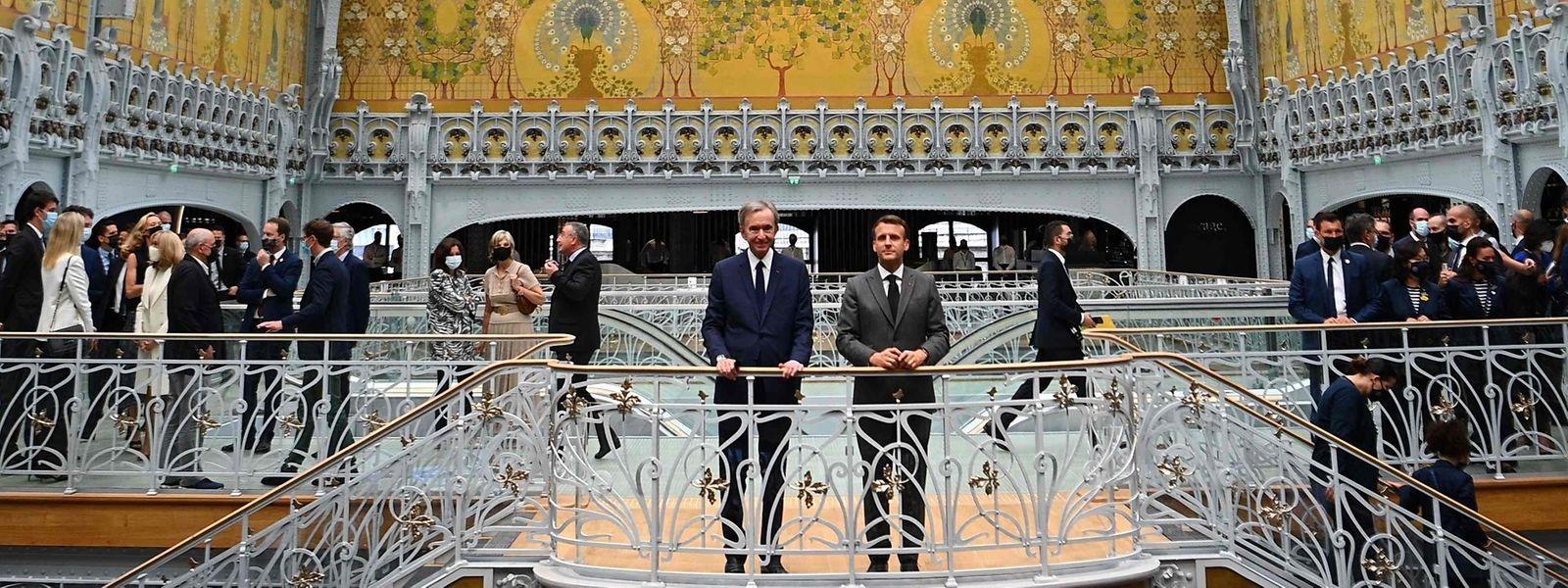 Der französische Präsident Emmanuel Macron (r) war als Überraschungsgast zur Eröffnung gekommen - hier mit LVMH- Direktor Bernard Arnault (l.)