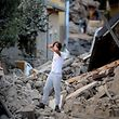 A man stands among damaged buildings after a strong earthquake hit central Italy, in Amatrice on August 24, 2016.  A powerful 6.2-magnitude earthquake devastated mountain villages in central Italy on August 24, 2016, left 38 people dead and the total is likely to rise, the country's civil protection unit said in the first official death toll. Scores of buildings were reduced to dusty piles of masonry in communities close to the epicentre of the pre-dawn quake in a remote area straddling the regions of Umbria, Marche and Lazio. / AFP PHOTO / FILIPPO MONTEFORTE