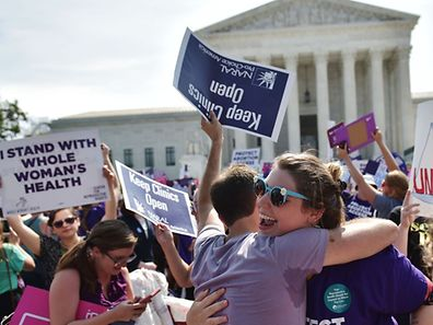 Abortion rights activists embrace after the US Supreme Court struck down a Texas law placing restrictions on abortion clinics