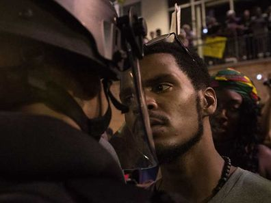 A protester stares at riot police during a demonstration against police brutality in Charlotte, North Carolina, on September 21, 2016, following the shooting of Keith Lamont Scott the previous day. A protester in Charlotte, North Carolina was fatally shot by a civilian during a second night of unrest after the police killed a black man, officials said. / AFP PHOTO / NICHOLAS KAMM