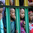Children watching the Deopokhari festival through the hole of Iron fence at Khokana, Patan, Nepal on August 20, 2016. The Deopokhari Festival starts at Khokana after brief Press Meet organized by Khokana Festival Committee, the members of Committee gave brief description about the festival, as the oppose against the negative messages flows on the news about the festival and the animal rights campaigners mentioning it as a Barbaric causes and live goat is ripped apart by villagers using their bare hands and teeth. According the committee; Devotees of different wards situated at Khokana participate in the festival, as a part of Newar culture and tradition; devotees of different wards jumps into the pond and struggle for a young female goat, as any groups of ward takes out from the pond, they declared as a winner and the groups have to initiate Culture traditional Music, Culture Dance etc. at Khokana. (Photo by Narayan Maharjan/NurPhoto via Getty Images)