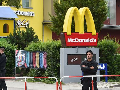 Policemen stand in front of a fast food restaurant on July 23, 2016 in Munich, southern Germany where took place the shooting near the Olympia-Einkaufszentrum shopping centre one day before. Police were probing the motives of the lone teenage German-Iranian gunman who went on a deadly rampage at a busy Munich shopping centre, the third bloody attack on civilians in Europe in just over a week. Nine people were killed and another 16 wounded as the black-clad gunman brought terror to Germany's third largest city on Friday evening, July 22, 2016, before committing suicide. / AFP PHOTO / Christof Stache