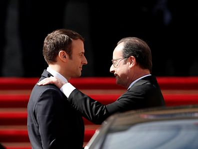 Former French President Francois Hollande (R) speaks to President Emmanuel Macron after the handover ceremony at the Elysee Palace in Paris, France, May 14, 2017.  REUTERS/Yoan Valat/Pool