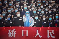Members of a medical assistance team from Jiangsu province chant slogans at a ceremony marking their departure after helping with the COVID-19 coronavirus recovery effort, in Wuhan, in China's central Hubei province on March 19, 2020. - Medical teams from across China began leaving Wuhan this week after the number of new coronavirus infections dropped. China on March 19 reported no new domestic cases of the coronavirus for the first time since it started recording them in January, but recorded a spike in infections from abroad. (Photo by STR / AFP) / China OUT
