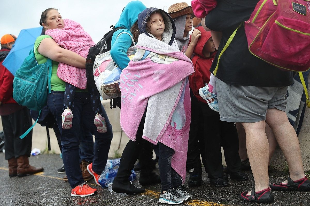 Evakuierte warten an auf ihren Abtransport. Sie haben nur das Nötigste eingepackt.