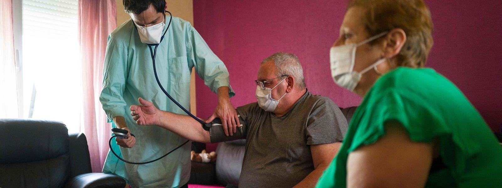 Ein Arzt untersucht einen Covid-19-Patienten in dessen Haus in Linsdorf, Frankreich.