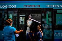 A nurse names people being tested for coronavirus inside a bus converted into a test lab at the Sao Domingos de Rana high school in Cascais on September 14, 2020. - A coronavirus bus travelled through several schools in Cascais in the outskirts of Lisbon to deliver free COVID-19 tests to teachers and school employees days before the beginning of the academic year. (Photo by PATRICIA DE MELO MOREIRA / AFP)
