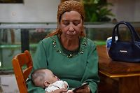 (FILES) This file photo taken on May 31, 2019 shows a Uighur woman holding a baby in a Uighur restaurant in Hotan in China's northwest Xinjiang region. - Chinese authorities are carrying out forced sterilisations of women in an apparent campaign to curb the growth of ethnic minority populations in the western Xinjiang region, according to research published on June 29, 2020. (Photo by GREG BAKER / AFP)
