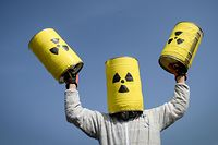 (FILES) In this file photo taken on March 12, 2017 a man carries fake nuclear barrels during a demonstration to demand the closure of Fessenheim nuclear power plant in Fessenheim, eastern France.  The Nuclear Nonproliferation Treaty (NPT), signed in 1968 by 191 countries, commits the five official holders of the atomic bomb (United States, Russia, France, Britain and China) to not transfer military nuclear technology to other countries, and prohibits non-nuclear countries from procuring or manufacturing nuclear weapons.  / AFP PHOTO / SEBASTIEN BOZON
