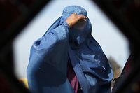 An Afghan woman is reflected in a mirror as she walks in Kabul February 11, 2013. REUTERS/Mohammad Ismail (AFGHANISTAN - Tags: SOCIETY)