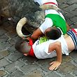 Participants fall next to Cebada Gago fighting bull on the third day of the San Fermin bull run festival in Pamplona, northern Spain on July 9, 2018. Each day at 8am hundreds of people race with six bulls, charging along a winding, 848.6-metre (more than half a mile) course through narrow streets to the city's bull ring, where the animals are killed in a bullfight or corrida, during this festival dating back to medieval times and also featuring religious processions, folk dancing, concerts and round-the-clock drinking.      / AFP PHOTO / ANDER GILLENEA
