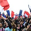 TOPSHOT - Supporters of French presidential election candidate for the En Marche ! movement Emmanuel Macron wave French national flags as they celebrate in front of the Pyramid at the Louvre Museum in Paris on May 7, 2017, following the announcement of the results of the second round of the French presidential election. Emmanuel Macron was elected French president on May 7, 2017 in a resounding victory over far-right Front National (FN - National Front) rival after a deeply divisive campaign, initial estimates showed. / AFP PHOTO / Eric FEFERBERG