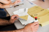 This illustration picture taken on June 23, 2019 shows an electoral official holding an envelope, a ballot paper and a stamp at a polling station during the mayoral election re-run in Istanbul. - Istanbul went back to the polls on June 23, 2019 in a re-run of the mayoral election that has become a test of Turkish democracy as well as Turkish President's continued popularity at a time of economic trouble. (Photo by GURCAN OZTURK / AFP)