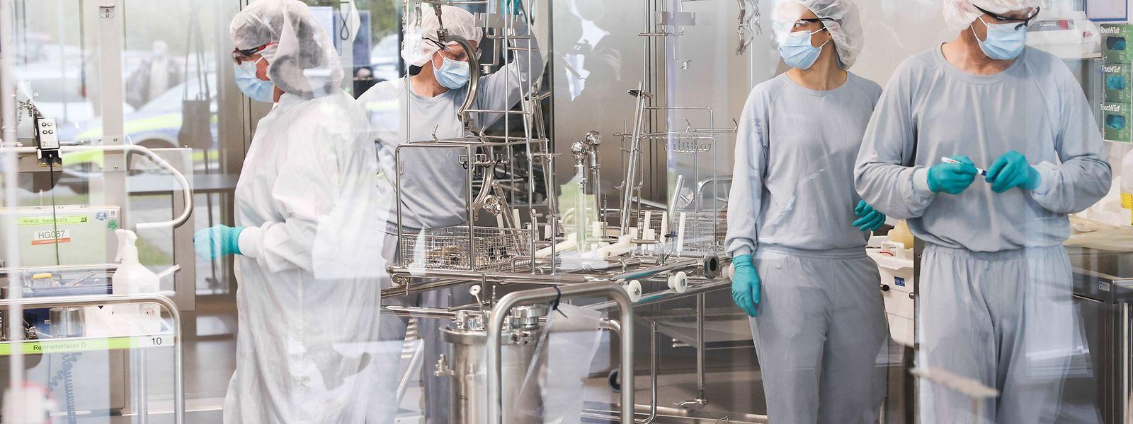 Mitarbeiterinnen und Mitarbeiter in Reinraumkleidung arbeiten in der Produktion des Impfstoffes Comirnaty von Biontech/Pfizer in den Produktionsstätten von Allergopharma in Reinbek.
