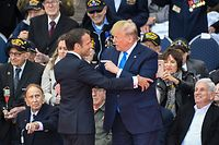 US President Donald Trump (R) and French President Emmanuel Macron hug in front of US WWII veterans during a French-US ceremony at the Normandy American Cemetery and Memorial in Colleville-sur-Mer, Normandy, northwestern France, on June 6, 2019, as part of D-Day commemorations marking the 75th anniversary of the World War II Allied landings in Normandy. (Photo by Damien MEYER / AFP)