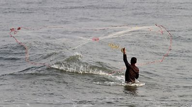 A fisherman casts his fishing net into the waters of the Arabian Sea in Kochi, India April 12, 2017. REUTERS/Sivaram V