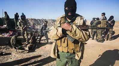 Ein maskierter Kämpfer der Hashed al-Shaabi bereitet sich auf den Kampf vor.