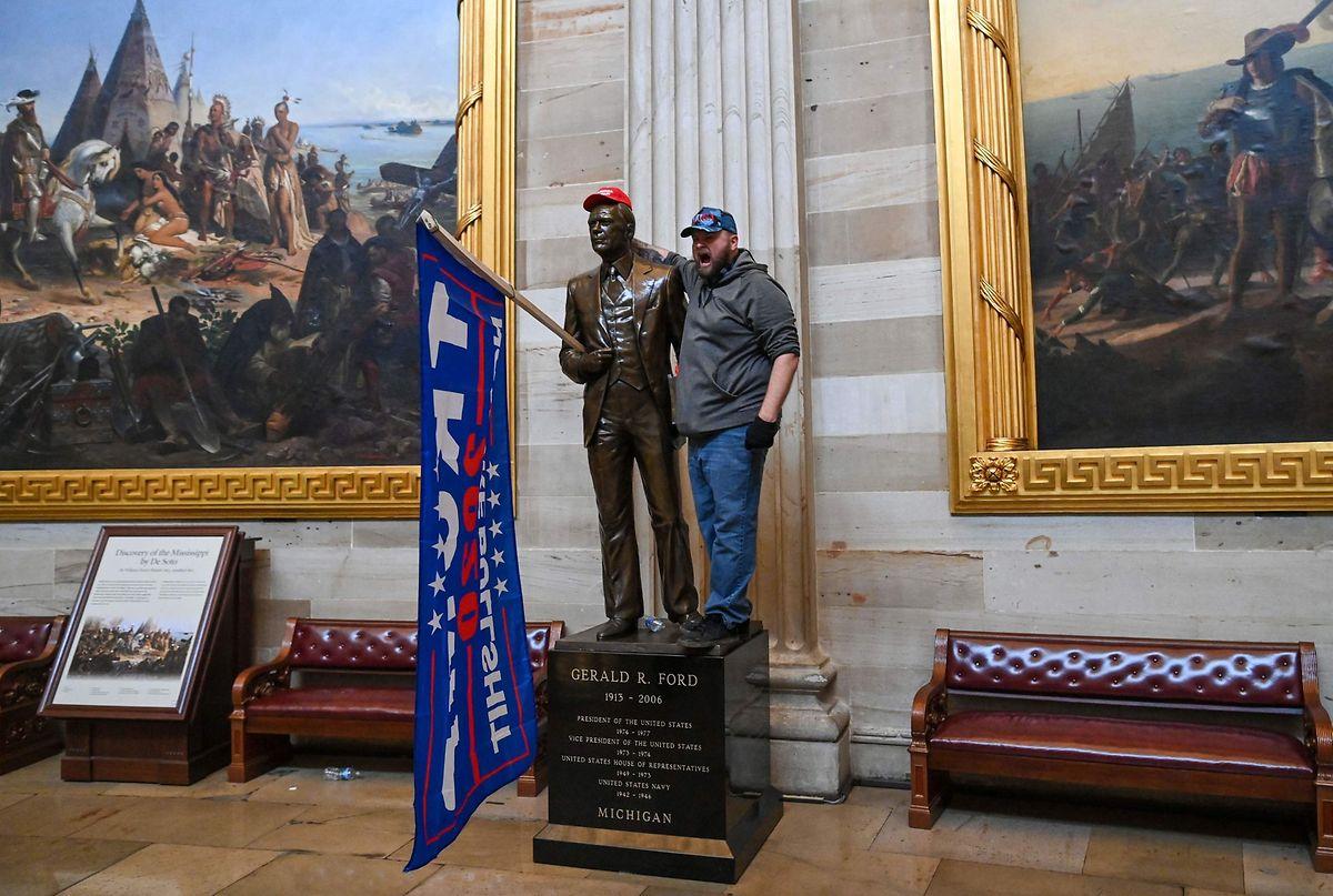 Ein Trump-Unterstützer lässt sich mit einer Statue von Ex-Präsident Gerald Ford fotografieren.Dieser hatte Richard Nixon begnadigt.