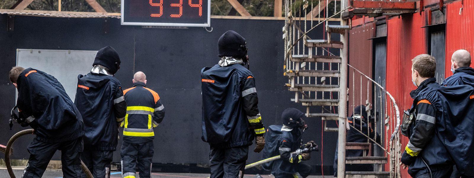 In den verrauchten Containern üben die Feuerwehrleute in Zweier-Teams mit je einem Trainer.