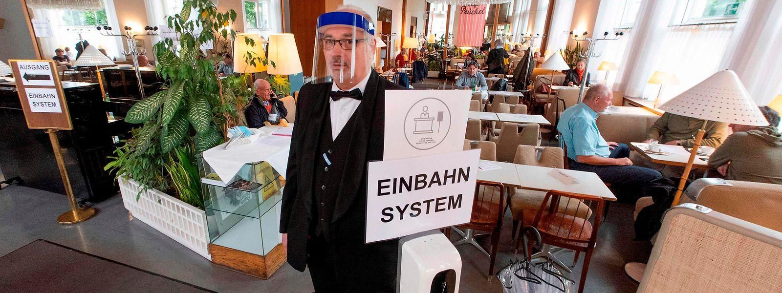 Einbahn-System: Ein Kellner mit Plexiglas-Schild des Cafe Prueckel in Wien weist den Gästen bei ihrer Ankunft den Weg.