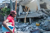 A Haitian woman cries as she passes a  destroyed house in Les Cayes on August 15, 2021, after a 7.2-magnitude earthquake struck the southwest peninsula of the country. - Hunched on benches, curled up in chairs or even lying the floor, those injured in the powerful earthquake that wreaked havoc on Haiti on Saturday crowded an overburdened hospital near the epicenter. The emergency room in Les Cayes, in southwestern Haiti, which was devastated by the 7.2-magnitude quake on Saturday morning that killed at least 724 people, is expecting reinforcements to help treat some of the thousands of injured. (Photo by Reginald LOUISSAINT JR / AFP)