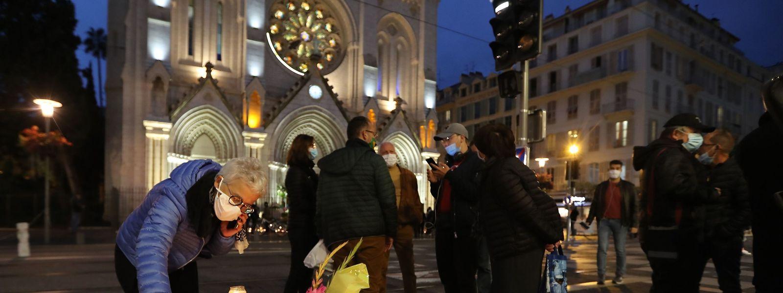 Vor der Kathedrale von Nice legen Passanten Blumen nieder.