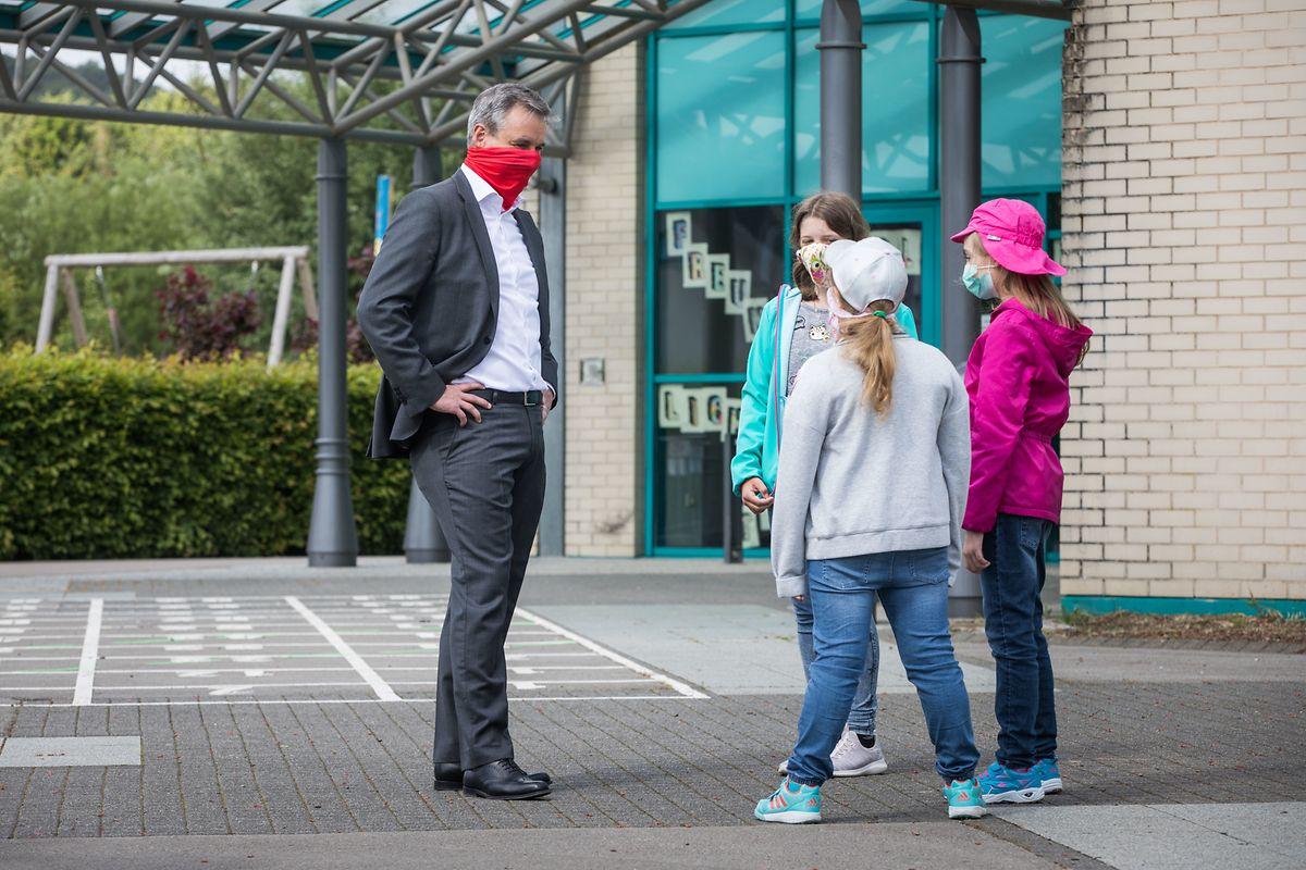 Claude Meisch im Gespräch mit jungen Schülerinnen.