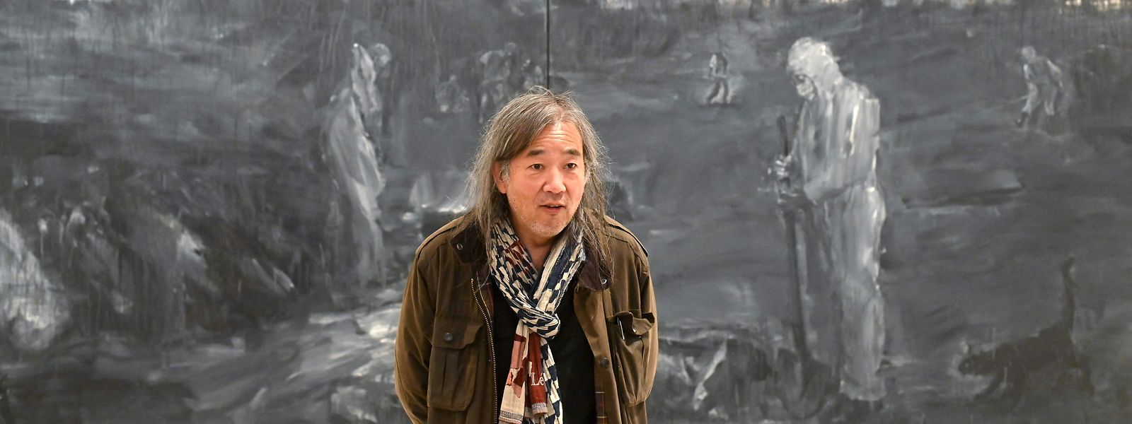 """Franco-Chinese painter, Yan Pei-Ming, stands in front of his painting entitled «Pandemie» (Pandemic) during a press visit to present the exhibition """"In the Name of the Father"""" devoted to his work at the Unterlinden museum in Colmar, eastern France, on March 31, 2021. (Photo by SEBASTIEN BOZON / AFP)"""