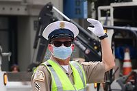 A Los Angeles traffic officer wear a mask as he directs traffic on March 24, 2020. - In California, already under orders to stay home, Governor Gavin Newsom tightened the lockdown to shut parking lots at beaches and parks after tens of thousands flouted social distancing rules. (Photo by Frederic J. BROWN / AFP)