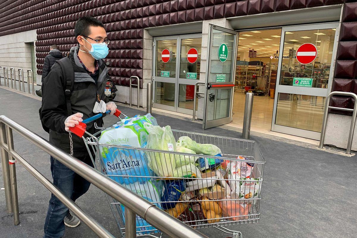 In Mailand kommt ein Kunde mit Mundschutz aus dem Supermarkt.