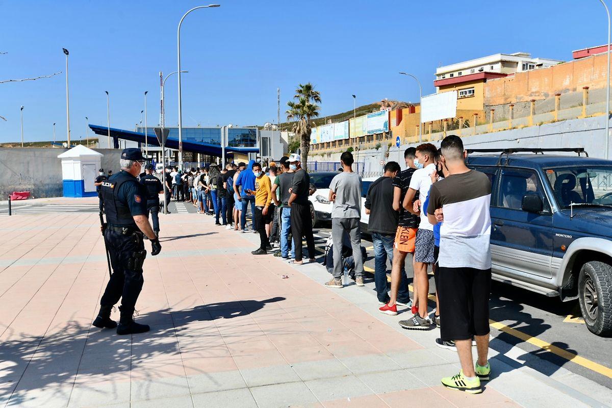Migranten aus Marokko stehen an den Toren der Grenze zu Ceuta Schlange, wo Beamte der spanischen Polizei Termine für Asylanträge ausgeben.