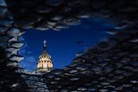 11.03.2020, Vatikan, Vatikanstadt: Die Spitze der Kuppel des Petersdoms spiegelt sich in einer Pfütze. Der Vatikan hat zum Schutz vor der Coronavirus-Welle am 10.03.2020 den Petersplatz für die Öffentlichkeit gesperrt. Foto: Evandro Inetti/ZUMA Wire/dpa +++ dpa-Bildfunk +++