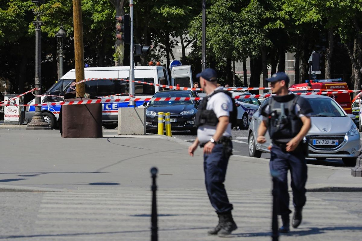 Police officers walk accross a sealed off area on June 19, 2017 on the Champs-Elysees avenue in Paris, after a car crashed into a police van  before bursting into flames.