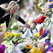 TOPSHOT - A young girl places a note among flowers left in tribute to victims in Christchurch, on March 17, 2019, two days after a shooting incident at two mosques in the city. - A right-wing extremist has been charged in the horrifying gun attacks on two New Zealand mosques, which left 49 people dead and dozens more injured. (Photo by Anthony WALLACE / AFP)