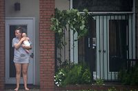 A woman holds a baby as she watches rising flood waters on the Cape Fear River during Hurricane Florence in Wilmington, North Carolina on September 14, 2018. - Florence smashed into the US East Coast Friday with howling winds, torrential rains and life-threatening storm surges as emergency crews scrambled to rescue hundreds of people stranded in their homes by flood waters. Forecasters warned of catastrophic flooding and other mayhem from the monster storm, which is only Category 1 but physically sprawling and dangerous. (Photo by ANDREW CABALLERO-REYNOLDS / AFP)