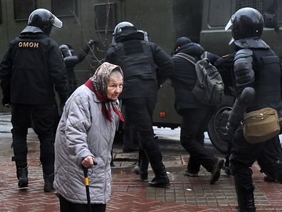 "An eldery woman walks along a street as riot police officers detain a man during a rally against President Alexander Lukashenko's rule and a controversial new tax on ""spongers"" - those who work less than six months a year - on March 25, 2017 in Minsk. / AFP PHOTO / Sergei GAPON"