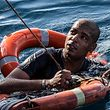 """TOPSHOT - A migrant is being rescued on January 4, 2019 with buoys and a rope, after he dived in the Mediterranean off Malta's coast from the Dutch-flagged Sea-Watch 3 rescue vessel, in a attempt to reach the shore by swimming. - Rights activists accused Europe on January 4, 2019 of clinching a new """"record of shame"""" with its refusal to open ports to migrant children and families stranded at sea in the Mediterranean. The Sea-Watch 3, a Dutch-flagged vessel which pulled the migrants to safety nearly two weeks ago, was on January 2 given permission by Malta to shelter off its coast from the fierce winds, but not to land. (Photo by FEDERICO SCOPPA / AFP)"""