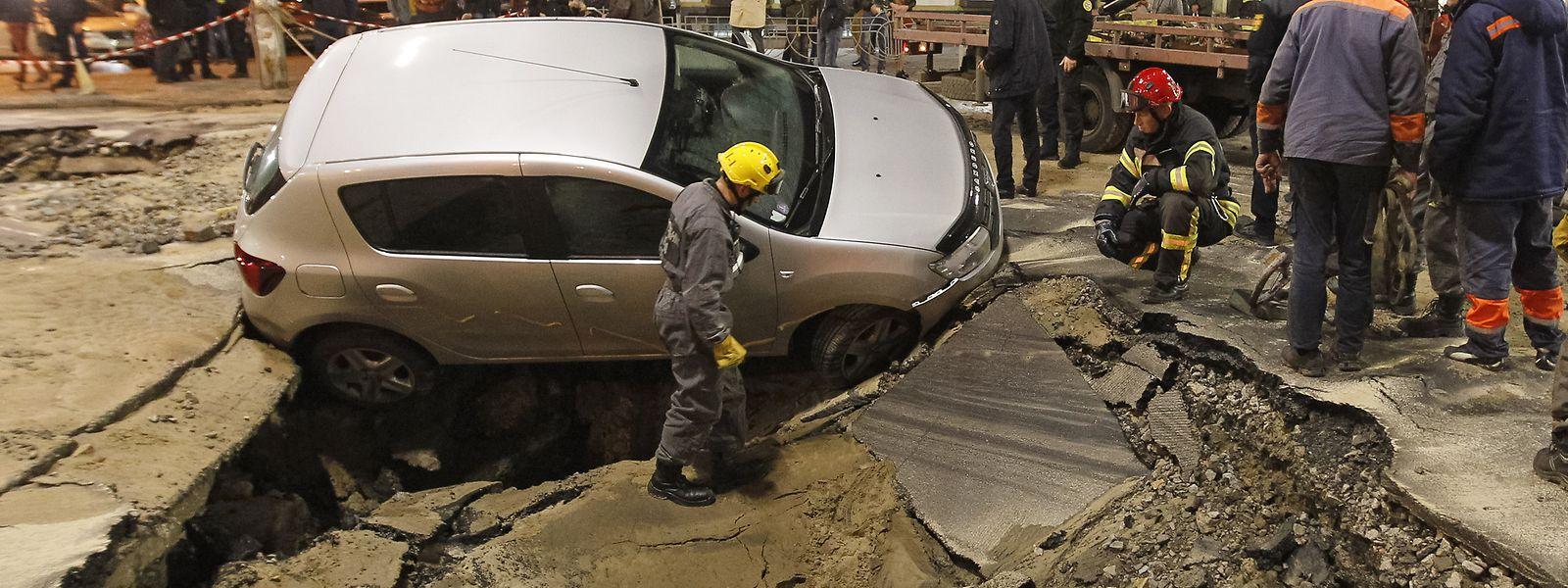 Einsatzkräfte stehen vor einem Auto, das auf einer Straße in Kiew in ein Loch gekippt ist.