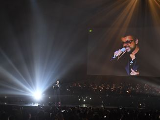 Chris Martin of British band 'Coldplay' (L) duets with a recording of late British pop icon George Michael (R) during the BRIT Awards 2017 ceremony and live show in London on February 22, 2017. / AFP PHOTO / Justin TALLIS / RESTRICTED TO EDITORIAL USE, TO ILLUSTRATE THE EVENT AS SPECIFIED IN THE CAPTION, NO POSTERS, NO USE IN PUBLICATIONS DEVOTED TO ARTISTS