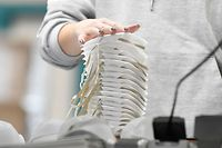"""An employee is piling up face masks of the category FFP2 before packing them at the plant of Moldex-Metric, a German producer of protective work wear, in Walddorfhaeslach, southern Germany, on January 20, 2021. - Germany on Tuesday, January 19, 2021 toughened a partial lockdown and extended it to February 14, with Chancellor Angela Merkel warning of possible border checks to contain """"the danger"""" of new coronavirus variants believed to be more contagious. Merkel and the state premiers also agreed to make medical masks mandatory on public transport and in shops -- meaning only surgical masks or the so-called FFP2 masks will be allowed. (Photo by THOMAS KIENZLE / AFP)"""