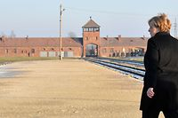 German Chancellor Angela Merkel walks in front of the main railway entrance to Birkenau as she visits the former German Nazi death camp Auschwitz-Birkenau in Oswiecim, Poland on December 6, 2019. - Merkel is on her first visit to the Auschwitz former German death camp, the site symbolising the Holocaust, in her 14 years as chancellor. Merkel is only the third German chancellor ever to visit the camp in Poland, with her landmark trip coming as Germany grapples with a resurgence of anti-Semitism and the growth of the far-right. (Photo by John MACDOUGALL / AFP)