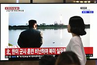TOPSHOT - A woman walks past a television news screen showing file footage of North Korean leader Kim Jong Un watching a missile launch, at a railway station in Seoul on July 31, 2019. - Pyongyang fired two ballistic missiles on July 31, Seoul said, days after a similar launch that the nuclear-armed North described as a warning to the South over planned joint military drills with the United States. (Photo by Jung Yeon-je / AFP)