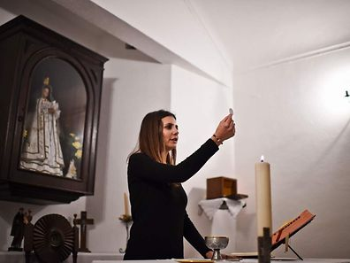 """Social worker and laywomen Claudia Rocha, (31) holds up the Hostia during the holy communion rite at Carrapatelo's church in Carrapatelo, Reguengos de Monsaraz, on February 18, 2017. Due to a shortage of catholic priests, laywomen lead """"Sunday celebrations"""" in churches of rural parishes as in the region of Reguengos de Monsaraz, southeastern Portugal, where there is only one clergyman for 16 villages. / AFP PHOTO / PATRICIA DE MELO MOREIRA"""
