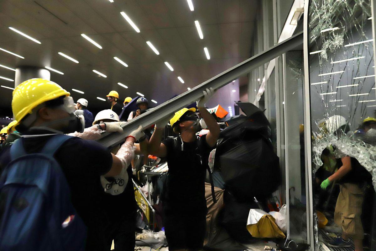 Demonstranten demolieren ein Fenster eines Regierungsgebäudes.