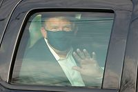 TOPSHOT - US President Trump waves from the back of a car in a motorcade outside of Walter Reed Medical Center in Bethesda, Maryland on October 4, 2020. (Photo by ALEX EDELMAN / AFP)