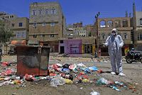 TOPSHOT - A Yemeni volunteer sprays disinfectant over garbage in the one of Sanaa's impoverished neighbourhoods, on March 30, 2020, amid concerns of a coronavirus outbreak. (Photo by MOHAMMED HUWAIS / AFP)