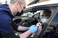 A nurse makes an injection of the Pfizer-BioNTech vaccine to a man in his car at a drive-in vaccination centre in Montpellier, on April 13, 2021, amid the sanitary crisis linked with the Covid-19 pandemic. (Photo by Pascal GUYOT / AFP)