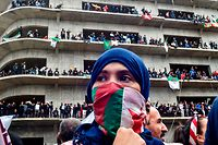 "A woman covers her face with the national flag, as Algerian protesters demonstrate in the capital Algiers against ailing president's bid for a fifth term on March 8, 2019. - Tens of thousands protested across Algeria today in the biggest rallies yet against ailing President Abdelaziz Bouteflika's bid for a fifth term, despite the defiant leader's warning of the risk of ""chaos"". (Photo by RYAD KRAMDI / AFP)"